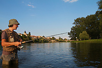 Arthur Fernandes fishing in the river Allier with the city in the background. Pont-du-Chateau, Auvergne, France.
