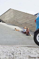 Three friends sitting on a staircase with dog and using a digital tablet, Munich, Bavaria, Germany