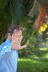 man holding his hand out in front of his face to block a photographer from taking his photograph