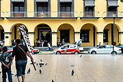 People walk past the city municipal building called the Palacio Municipal San Andres Tuxtla in San Andres Tuxtlas, Veracruz, Mexico.