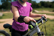 Mariella Anderson rides her bike at the Carver Lake Park mountain bike Skills Park in Woodbury, Minnesota on Tuesday, Aug. 4, 2020.