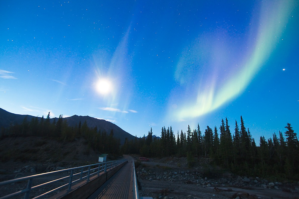 The northern lights and the moon at night above the footbridge to McCarthy, Alaska.