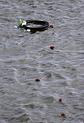 29 August 2006. New Orleans, Louisiana. Lower 9th ward. Great Flood commemoration and memorial ceremony; to 'honor and remember our loved ones who have passed.' <br /> The memorial wreath floats from the industrial canal bridge, close to the levee breach which destroyed the Lower 9th ward. The wreath was dropped from the bridge into the water.<br /> Photo Credit©; Charlie Varley/varleypix.com