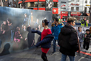 Passers-by walk past a publicity banner for the new film Fantastic Beasts: The Crimes of Grindelwald, hours before its UK premier in Leicester Square, on 13th November 2018, in London, England.