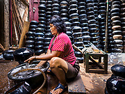 """28 MARCH 2017 - BANGKOK, THAILAND: A woman washes newly made monks' bowls, called """"bat"""" (pronounced with a long """"a"""" as in baat) on Soi Baan Bat in Bangkok. The bowls are made from eight separate pieces of metal said to represent the Buddha's Eightfold Path. The Monk's Bowl Village on Soi Ban Baat in Bangkok is the only surviving one of what were originally three artisan's communities established by Thai King Rama I for the purpose of handcrafting """"baat"""" the ceremonial bowls used by monks as they collect their morning alms. Most monks now use cheaper factory made bowls and the old tradition is dying out. Only six or seven families on Soi Ban Baat still make the bowls by hand. Most of the bowls are now sold to tourists who find their way to hidden alleys in old Bangkok. The small family workshops are only a part of the """"Monk's Bowl Village."""" It is also a thriving residential community of narrow alleyways and sidewalks. The area is also spelled Ban Bat or Baan Bat.           PHOTO BY JACK KURTZ"""