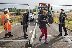 An anti-HS2 activist is guided through fencing by police officers after having occupied a trailer being used to transport wood chip in order to try to prevent or delay tree felling alongside the Fosse Way in connection with the HS2 high-speed rail link on 24th August 2020 in Offchurch, United Kingdom. The controversial HS2 infrastructure project is currently expected to cost £106bn and will destroy or significantly impact many irreplaceable natural habitats, including 108 ancient woodlands.