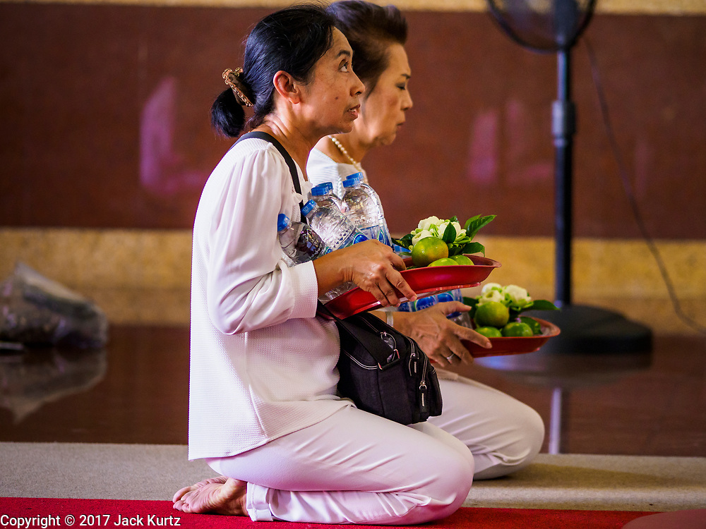 20 OCTOBER 2017 - BANGKOK, THAILAND: Women pray in a Chinese shrine on Yaowarat Roadon the first day of the Vegetarian Festival, what Thais call the Taoist Nine Emperor Gods Festival, in the Chinatown neighborhood of Bangkok, Thailand. It is a nine-day Taoist celebration beginning on the eve of 9th lunar month of the Chinese calendar. For nine days people participating in the festival wear only white and don't eat meat, poultry, seafood, and dairy products. The vegetarian festival is celebrated throughout Thailand, but especially in Phuket and Bangkok, cities with large ethnic Chinese communities.       PHOTO BY JACK KURTZ