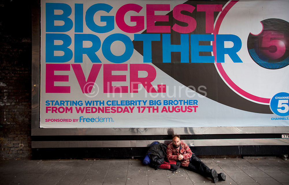A homeless man lying underneath a billboard advertising poster for the latest series of Big Brother. The new series of the celebrity version of the hit TV show starts on Chanel 5 in the UK on 17th August 2011. The feeling of surveillance and the contrasting life of the man in the picture shows a stark reality of rich and poor. Of celebrity and man on the street, quite literally