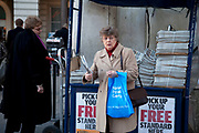 Woman picks up her copy of the free The Evening Standard Newspaper. Once this paper cost 50pence but in competiotn with other free London newspapers, teh standard changed it's approach.