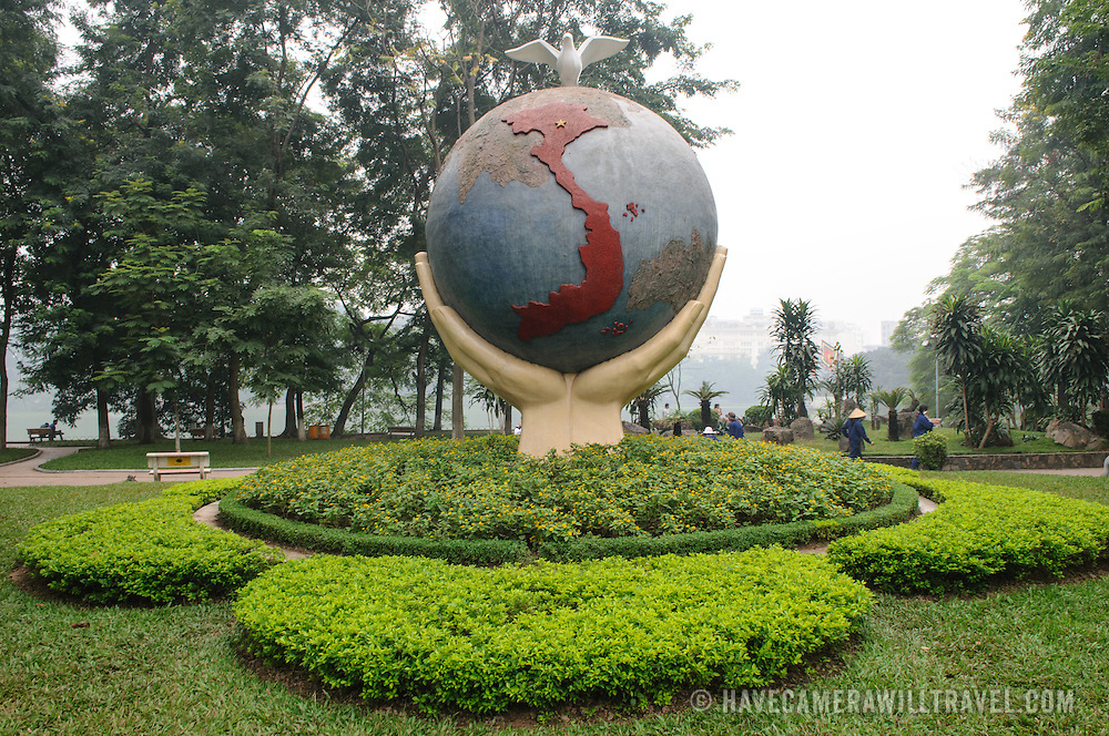 """An art sculpture of a globe with hands and a dove on the shore of Hoan Kiem Lake in Hanoi, Vietnam. The sculpture is titled """"Hope & Love for Peace."""""""