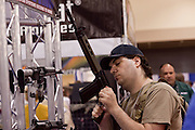 16 MAY 2009 -- PHOENIX, AZ: A man looks at a civilian version of the FN-FAL military rifle in a booth at the NRA convention in Phoenix Saturday. The booths that displayed military style firearms were extremely busy at the convention as many gun owners expressed concern about the Obama administration's policies on gun ownership. About 60,000 people were expected to attend the trade show at the 138th annual National Rifle Association Annual Meeting in the Phoenix Convention Center in Phoenix, AZ. Photo by Jack Kurtz