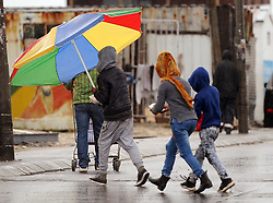 Cape Town - 180630 -Three children share a beach umbrella on a trip to the spaza shop on Vrygrond Avenue, Vrygrond - Photographer - Tracey Adams/African News