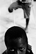 A boy whose father is an amputee. Makeni resettlement camp for amputees, Makeni, Sierra Leone 2004<br /> Rebel forces, the Revolutionary United Front in Sierra Leone, systematically murdered, mutilated, and raped civilians during the country's civil war as a policy of terror