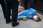 Extinction Rebellion protester falls to the ground as she is detained and handcuffed by police for throwing red paint to mimick blood onto the outside the Brazilian Embassy on 7th September 2020 in London, United Kingdom. Extinction Rebellion is a climate change group started in 2018 and has gained a huge following of people committed to peaceful protests. These protests are highlighting that the government is not doing enough to avoid catastrophic climate change and to demand the government take radical action to save the planet.
