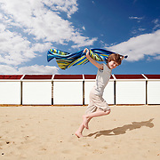 A young boy photographed running on a bright, empty, sandy beach. Shot for a healthcare advert in the uk by photographer Stuart Freeman.