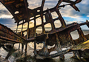 Shipwreck skeleton at sunset. In 1906, the crew of the sailing ship Peter Iredale took refuge at Fort Stevens, after she ran aground on Clatsop Spit. The wreck is visible today, within Fort Stevens State Park, along the Oregon Coast, USA. Active from 1863–1947, Fort Stevens was an American military installation that guarded the mouth of the Columbia River in the state of Oregon. Built near the end of the American Civil War, it was named for a slain Civil War general and former Washington Territory governor, Isaac I. Stevens. Multiple overlapping photos were stitched to make this panorama.