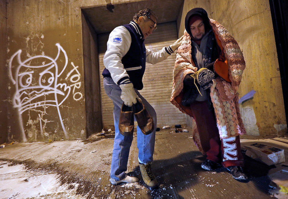 Dr. Patrick Angelo hands over the shoes off his feet to help a homeless man under the overpasses on Lower Wacker Drive in Chicago, Illinois, January 7, 2014. Angelo visits the homeless several times a week to hand out food, clothing and blankets to those living on the streets with the funding coming from his oral surgery medical practice and profits from his healthcare company. Angelo is in his 13th year doing his charity work.  Picture taken January 7.  REUTERS/Jim Young