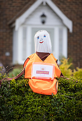 © Licensed to London News Pictures. 27/04/2020. Capel, UK. A scarecrow depiction of a postal worker sits outside a house in the Surrey village of Capel. Residents of the village have resurrected their summer tradition of scarecrows in tribute to NHS medical staff and other key workers. Up to 30 of the life size home made doll like characters can be seen in front gardens throughout the village. The public have been told they can only leave their homes when absolutely essential, in an attempt to fight the spread of coronavirus COVID-19 disease. Photo credit: Peter Macdiarmid/LNP