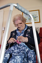 View through a walking frame of an elderly woman knitting at home,
