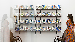 "© Licensed to London News Pictures. 01/09/2020. LONDON, UK. A staff member poses with ""The Complete Set of 20 »Visage« plates"", 1963, all by Pablo Picasso.  Preview of ""Atelier Picasso"", a new exhibition recreating Pablo Picasso's studio in Cannes featuring his drawings, prints, ceramics and furniture.  The show is at Bastian gallery in Mayfair 3 September to 31 October 2020.  Visitors will be required to wear a facemask and practice social distancing.  Photo credit: Stephen Chung/LNP"