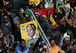 Mandela Memorial Service.<br /> 60813443<br /> Supporters hold a poster of Nelson Mandela before the memorial service for the former South African president at the FNB Stadium in Soweto near Johannesburg, South Africa, Tuesday, 10th December 2013. Picture by  imago / i-Images<br /> <br /> UK ONLY