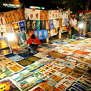 A woman looks after her stall selling paintaings, drawings, and other illustrations laid out on the ground on on boards at the night market on Quai Fa Ngum on the banks of the Mekong in Vientiane, Laos.