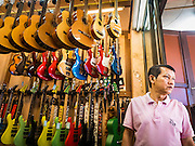 07 JUNE 2016 - BANGKOK, THAILAND: A worker in a guitar shop waits for customers in Verng Nakorn Kasem, also known as the Thieves' Market. Verng Nakorn Kasem was one of Bangkok's most famous shopping districts. It is located on the north edge of Bangkok's Chinatown, it grew into Bangkok's district for buying and selling musical instruments. The family that owned the land recently sold it and the new owners want to redevelop the famous area and turn it into a shopping mall. The new owners have started evicting existing lease holders and many of the shops have closed. The remaining shops expect to be evicted by the end of 2016.   Bangkok's Chinatown, considered by some to be one of the best preserved Chinatown districts in the world, is changing. Many of the old shophouses are being demolished and replaced by malls and condominium developments.        PHOTO BY JACK KURTZ