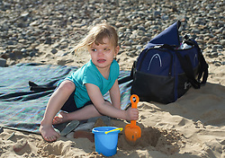© Licensed to London News Pictures. 28/03/2012..Saltburn, England..As temperatures rise this week the beach at Saltburn in Cleveland attracts the visitors as they enjoy the warm weather. Katie Cuthbert, 3 from Stockton plays in the sand...Photo credit : Ian Forsyth/LNP