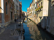 Pedestrians walking next to a lovely Venice canal on a beautiful sunny day