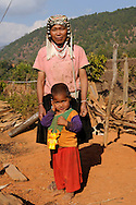 Burma/Myanmar, Golden Triangle. Akha woman staying with a child.