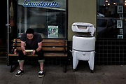Man drinking coke and reading a book waiting for washing to be done in laundromat laundrette next to old fashioned washing machine in Oakland, California