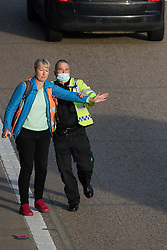 Ockham, UK. 21st September, 2021. An Insulate Britain climate activist walks into the clockwise carriageway of the M25 between Junctions 9 and 10 as part of a campaign intended to push the UK government to make significant legislative change to start lowering emissions. Both carriageways were briefly blocked before being cleared by Surrey Police. The activists are demanding that the government immediately promises both to fully fund and ensure the insulation of all social housing in Britain by 2025 and to produce within four months a legally binding national plan to fully fund and ensure the full low-energy and low-carbon whole-house retrofit, with no externalised costs, of all homes in Britain by 2030.
