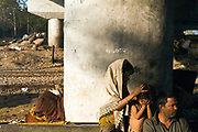 A child picks at her sister's hair for fleas on a piece of waste ground beneath a flyover near Okhla station. New Delhi, India