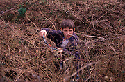 AE2CG5 Young boy cutting brambles in overgrown garden