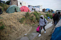 © Licensed to London News Pictures. 24/10/2016. Calais, France. A migrant carry his belongings past tents in the camp as the evacuation and demolition begins of the migrant camp in Calais, known as the 'Jungle'. French authorities have given an eviction order to thousands of refugees and migrants living at the makeshift living area of the French coast. Photo credit: Ben Cawthra/LNP