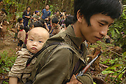 Song Tua Ya, carries his AK47 and young son while maintaining village security, near Vang Vieng, Laos, July 4, 2006...**EXCLUSIVE, no tabloids without permission**  .Pictured are a group of Hmong people who report an attack against them April 6, 2006 by Lao and Vietnamese military forces.  26 people perished, 5 were injured, and 5 babies died shortly after because their dead mothers could not breast-feed them.  Only one adult male was killed, the other 25 victims were women and children (17 children).  The Lao Spokesman for the Ministry of Foreign Affairs says this is a fabrication, an investigation has been completed, and there was no attack.  The Hmong group says no officials have interviewed witnesses or visited the crime scene, a point the Lao Spokesman did not deny.  ..The Hmong people pictured have hidden in remote mountains of Laos for more than 30 years, afraid to come out.  At least 12,000 are said to exist, with little food, scavenging in the jungle. Most have not seen the modern world.  Since 1975, under the communists, thousands of reports evidence the Hmong have suffered frequent persecution, torture, mass executions, imprisonment, and possible chemical weapons attacks.  Reports of these atrocities continue to this day.  The Lao Government generally denies the jungle people exist or that any of this is happening.  The Hmong group leader, Blia Shoua Her, says they are not part of the Hmong resistance and want peace.  He claims they are just civilians defending their families, hoping to surrender to the UN..