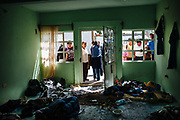 People watch inside of a room that was used to hide migrants kidnapped by a group of criminals and the police, in Lara Grajales, Mexico, October 13, 2008.