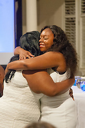 Tamika Turnbull gets a hug by fellow graduate Inzinga Smith.  Ten graduates of the University of the Virgin Islands School of Nursing commemorated their graduation with a pinning ceremony and lighting of candles while surrounded by nursing alumni, family, and friends.  University of the Virgin Islands School of Nursing 2015 Pinning Ceremony.  St. Thomas Reformed Church.  St. Thomas, VI.  12 May 2015.  © Aisha-Zakiya Boyd