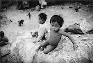 Children from a squalid, mobile community on the edge of Chong Kneas which will follow the receding waters of Tonle Sap as the dry season commences, Cambodia.