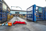 Birmingham, United Kingdom, June 14, 2021: An activist appears to be chaining and glueing herself outside the entry gates of an American industrial company admin office specializing in lightweight metals engineering and manufacturing known as Arconic in Bermingham on Monday, June 14, 2021.  (Photo by Vudi Xhymshiti)
