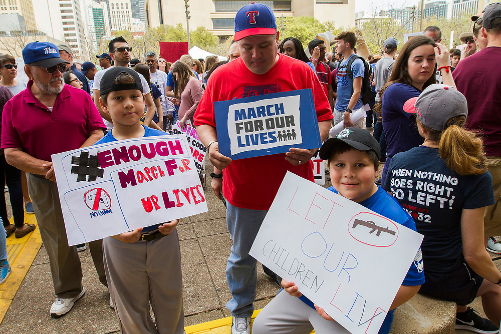 Robert Pacheco (center) and his two sons Ethan,8 , left and Ryan, 7, right, protest current lack of gun legislation durng ther March for Our Lives event at Dallas City Hall on Saturday.