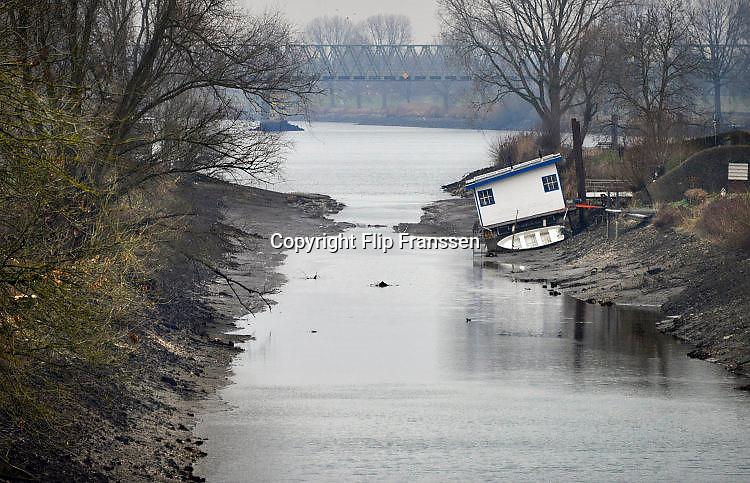 Nederland, The Netherlands, Mook, 3-1-2017In Mook is recreatieplas de Mookerplas niet meer bereikbaar vanaf de Maas. Het water is te ver gezakt. Wel probeert men het leeglopen van de plas te stoppen door planken met plastic in de sluisopening aan te brengen. Het haventje van Mook ligt droog en een woonboot ligt scheef op de oever. Rijkswaterstaat heeft twee waterpompen laten aanrukken om vanuit de Maas water te pompen in het Maas-waalkanaal. Hierdoor kan het stuk tot aan de rivier de Waal, waaronder een industriegebied bij Nijmegen, weer bevaren worden. De pompen hebben een capaciteit van 1400 liter per seconde.Foto: Flip Franssen