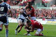 Cardiff Blues player Josh Navidi is tackled by George North and Josh Turnbull of the Scarlets (7). Rabodirect Pro12 rugby, Scarlets v Cardiff Blues at the Parc y Scarlets in Llanelli, South Wales on Saturday 20th April 2013. pic by Andrew Orchard,  Andrew Orchard sports photography,