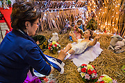 24 DECEMBER 2013 - BANGKOK, THAILAND: A woman washes the feet of a doll that represents the Baby Jesus in a nativity scene during Christmas services at Holy Redeemer Church in Bangkok. Thailand is predominantly Buddhist but Christmas is widely celebrated throughout the country. Buddhists mark the day with secular gift giving but there are about 300,000 Catholics in Thailand who celebrate religious Christmas. Catholics first came to Thailand (then Siam) in 1567 as chaplain for Portuguese mercenaries in the employ of the Siamese monarchy. There has been a continuous Catholic presence in Thailand since then.   PHOTO BY JACK KURTZ