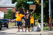 Two Pride Rally participants stand with raised fists at the intersection of  PA Routes 405 and 642 in Milton, Pennsylvania on August 8, 2020. The I Am Alliance organized the event to show support for the LGBTQ community.