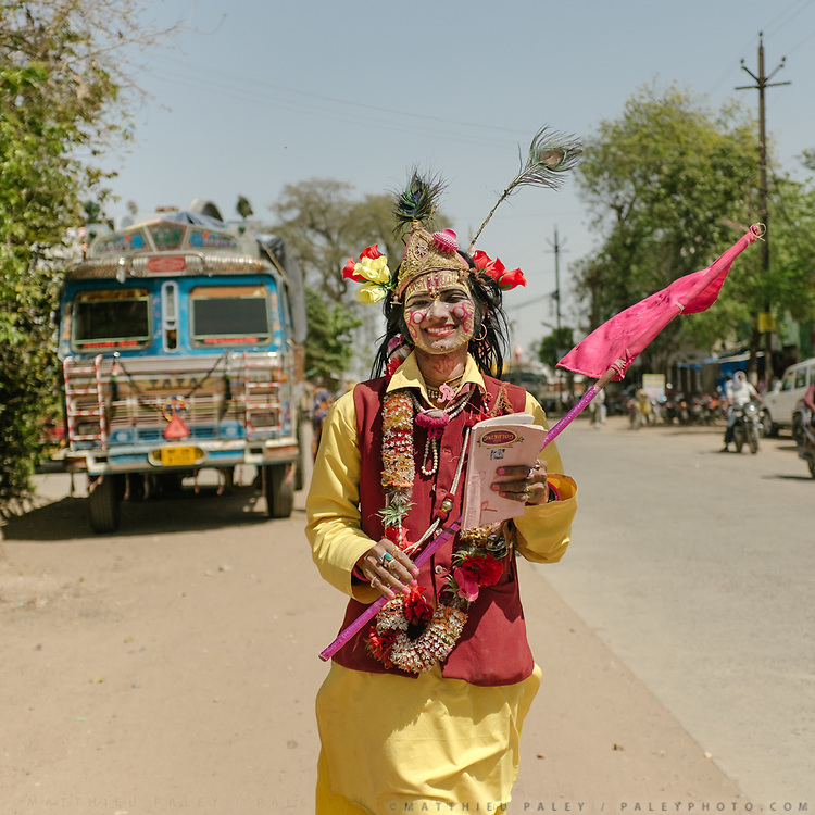 """You couldn't miss him—such colors! On his throat is written the word """"Krishna."""" He is a traditional performance artist known as a behurupiya. """"I am Raje Krishna on my way to the temple, that's who I am!""""<br /> Rajasthan Province."""