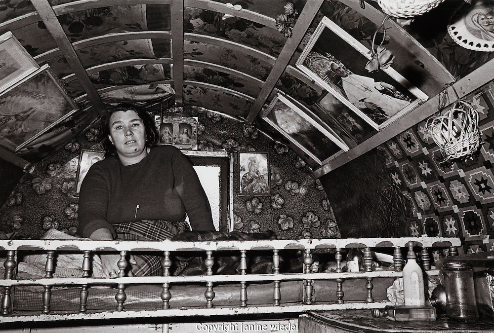 Irish Tinker woman sitting on platform bed inside her bow shaped wooden traditional  caravan.