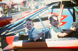 two boys enjoying a ride at an amusement park