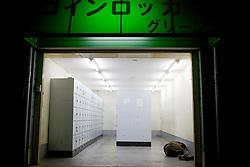 A  man sleeps in coin locker in Kamagasaki, Japan.