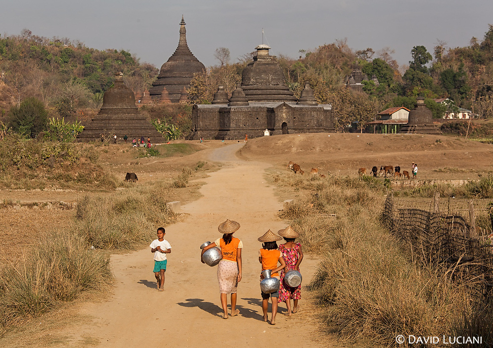Girls with aluminium water pots walking to the water place near the main temple complex in Mrauk U.